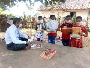 दीनदयाल शोध संस्थान के कार्यकर्ता गांव-गांव बच्चों को पाठ्य सामग्री वितरण कर रहे